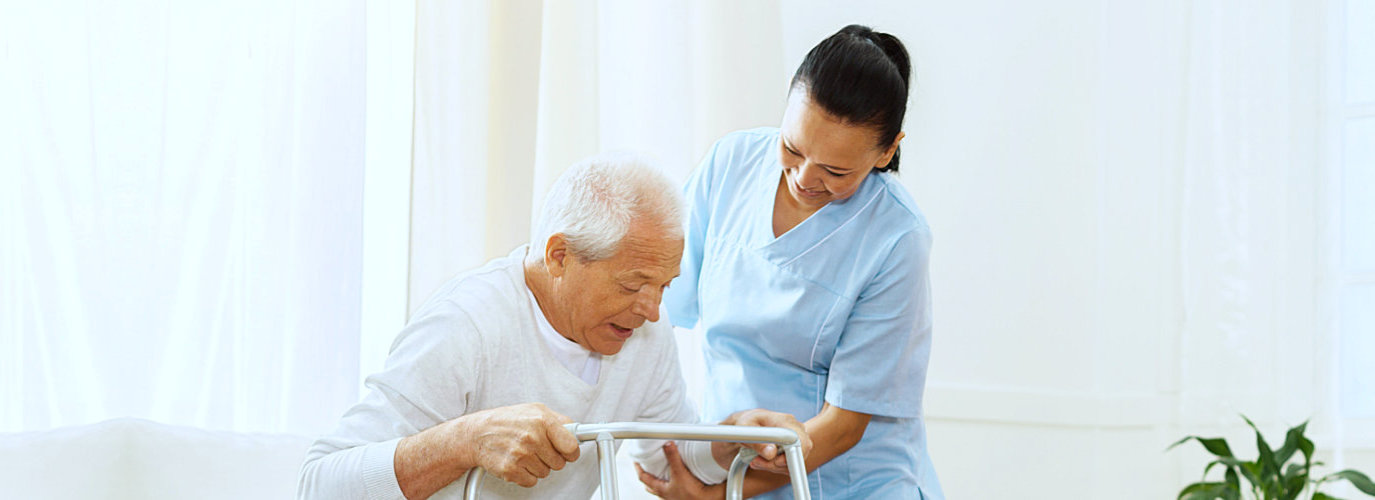 female caregiver assisting senior man to stand indoor