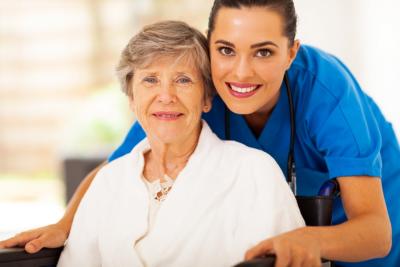 caregiver hugging senior woman on a wheelchair